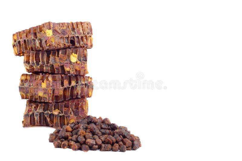 Os grânulo do pão da abelha e uma parte de pilhas do mel são isolados em um fundo branco Remédio natural para o realce da imunida imagem de stock
