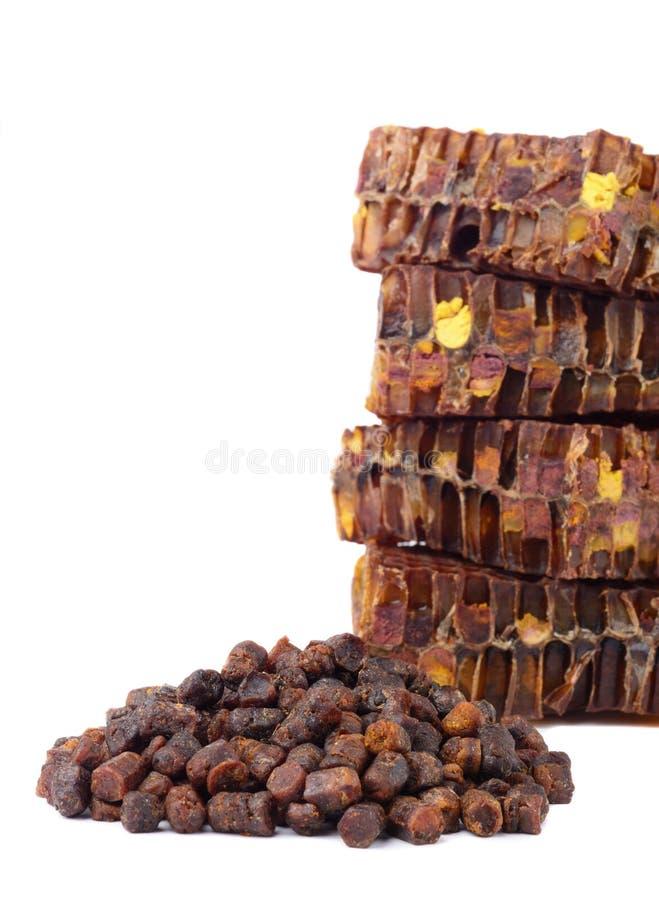 Os grânulo do pão da abelha e uma parte de pilhas do mel são isolados em um fundo branco Remédio natural para o realce da imunida foto de stock royalty free
