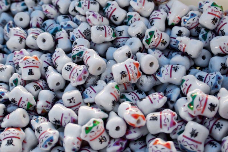 Os grânulos asiáticos de vidro multicoloridos dos gatos formam um teste padrão imagens de stock royalty free