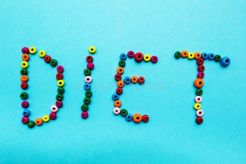 os grânulos das crianças Multi-coloridas, dispersados em um fundo azul A palavra foto de stock royalty free