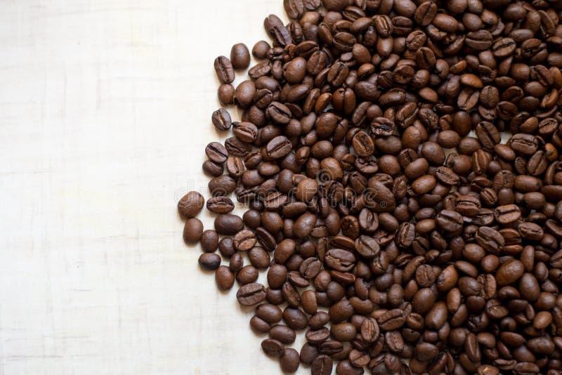 Os grãos de café pretos encontram-se na tabela de madeira clara, imagem de fundo Lugar para o texto imagens de stock royalty free