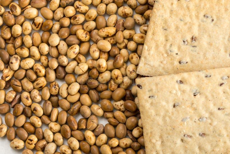 Os grãos de soja com linho lascam-se no fundo de mármore branco fotografia de stock