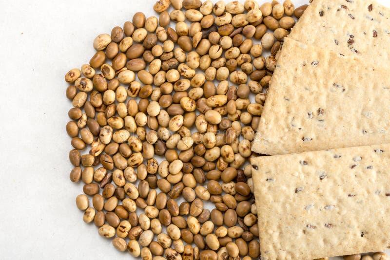 Os grãos de soja com linho lascam-se no fundo de mármore branco foto de stock royalty free