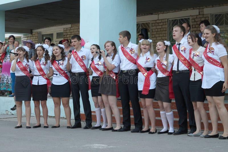 Os graduados da escola estão cantando uma música fotos de stock