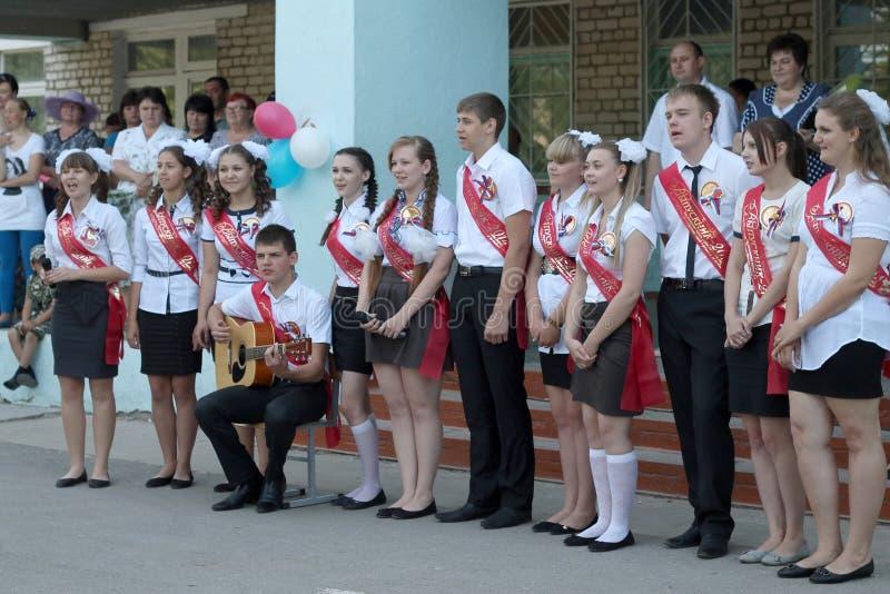 Os graduados da escola estão cantando uma música com uma guitarra foto de stock