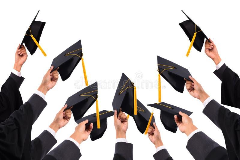 Os graduados da universidade, dos graduados que guardam chapéus entregaram a fotografia de stock royalty free