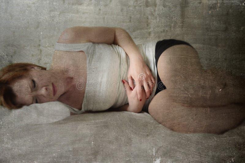 Os grampos de estômago de sofrimento da mulher bonita nova na barriga que guarda o grunge editam foto de stock royalty free