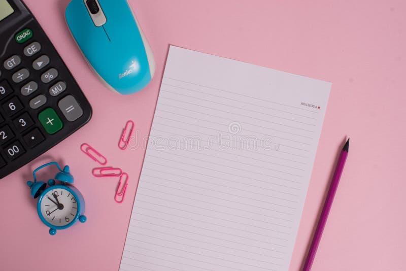 Os grampos portáteis da calculadora eletrônica prendem o fundo colorido do tamanho da letra do lápis da excitação do despertador  foto de stock