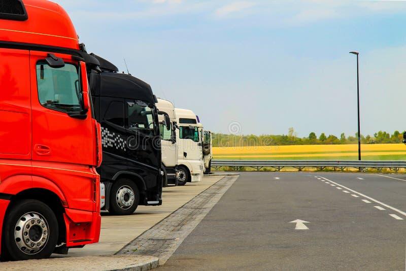 Os grandes caminhões de vermelho, preto e branco são estacionados perto da estrada Conceito do fornecimento ou da fonte Trem de e imagens de stock