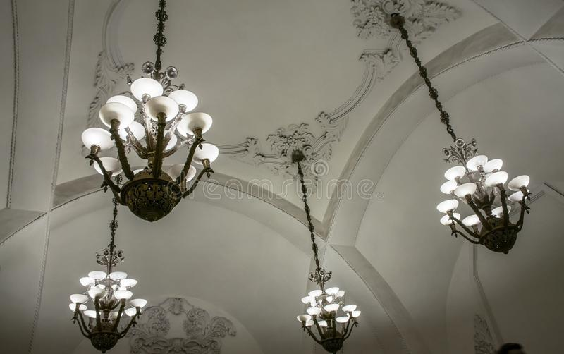 Os grandes candelabros luxuosos sob o ornamental arquearam o teto imagem de stock