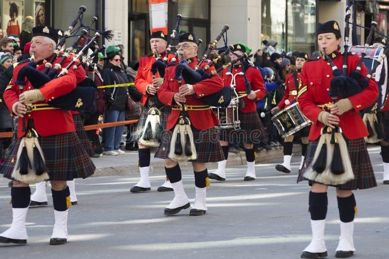 Os grandes jogadores da gaita de fole das montanhas no uniforme escocês tradicional no dia do ` s de Montreal St Patrick desfilam fotografia de stock