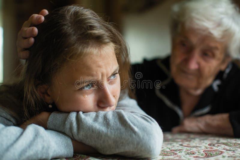 Os gritos adolescentes da menina, avó acalmam e afagam sua cabeça Fam?lia fotos de stock royalty free