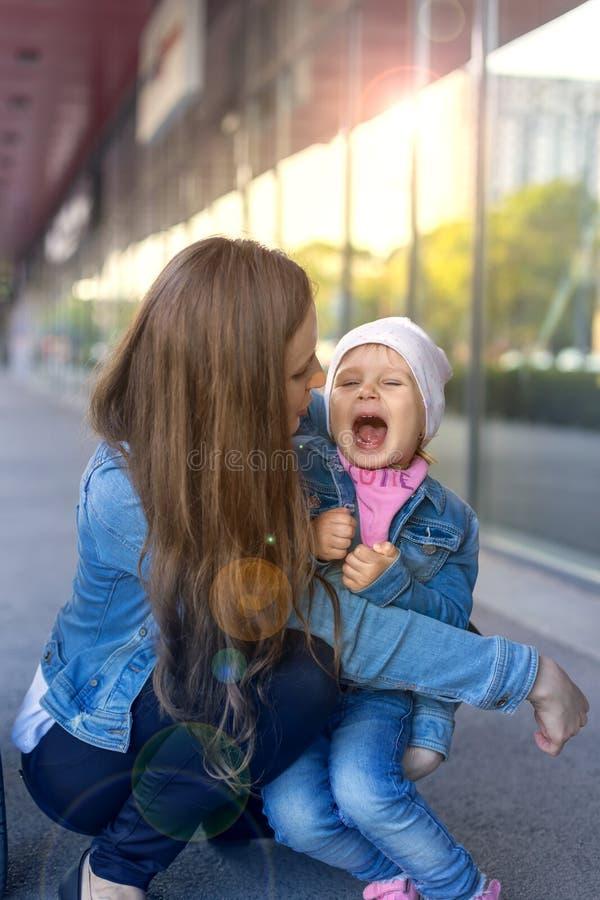Os gritos da criança e a mãe abraçam-no fotos de stock
