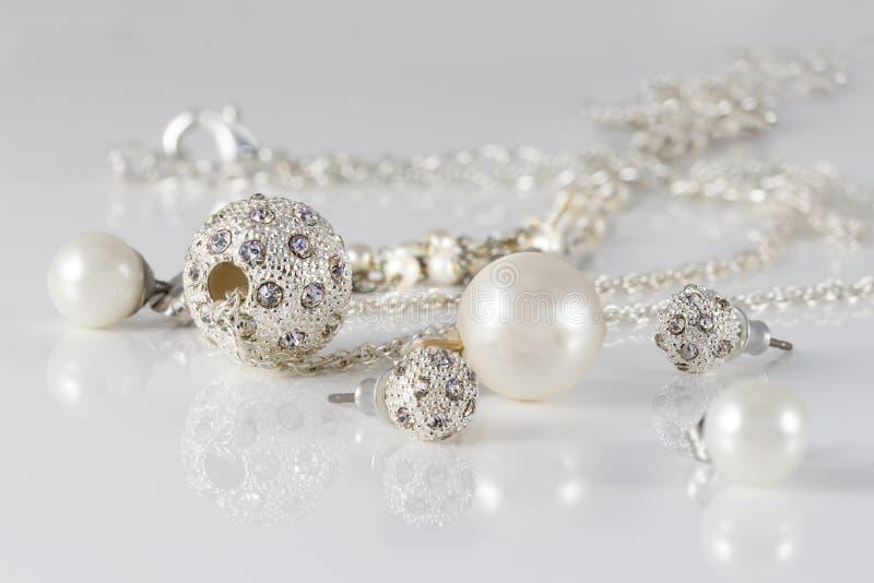 Os grupos da joia do close up de brincos e de pendentes de prata enchidos no acrílico surgem no fundo cinzento imagem de stock