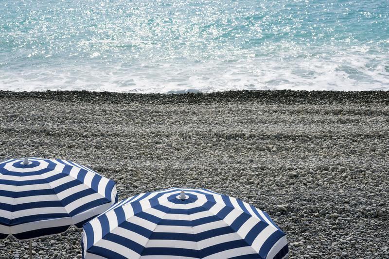 Os guarda-chuvas azuis e brancos listrados em um Pebble Beach em Promenade des Anglais em agradável, França, esperam convidados foto de stock