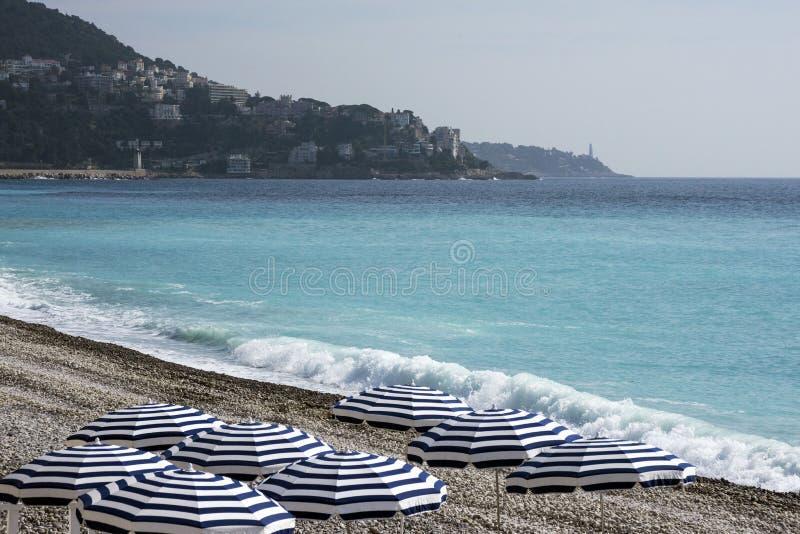 Os guarda-chuvas azuis, tabelas reservados com toalhas de mesa brancas no Pebble Beach de Promenade des Anglais em agradável, Fr fotos de stock royalty free