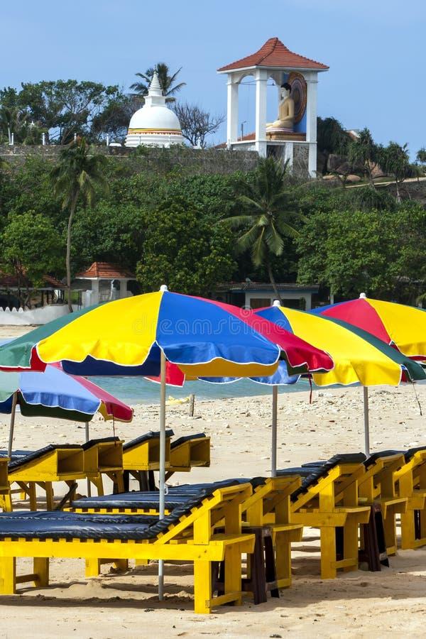 Os guarda-chuvas de praia estabelecem-se na praia de Unawatuna na costa sul de Sri Lanka cedo na manhã imagens de stock