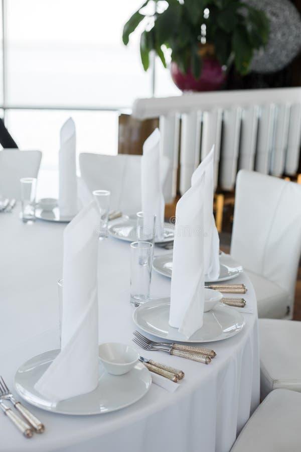 Os guardanapo brancos do close up estão nas placas brancas na tabela servida no restaurante disposição branca limpa dos pratos em imagem de stock royalty free