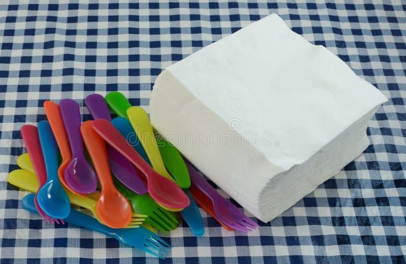 Os guardanapo de papel e o faqueiro plástico para o piquenique party fotografia de stock