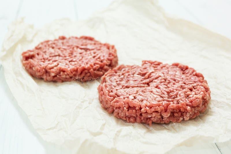 Os Hamburger crus fizeram da carne de porco orgânica em um fundo de madeira branco foto de stock