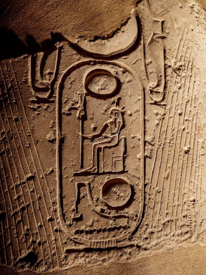 Os hieróglifos antigos que descrevem pharaohs nomeiam em uma coluna em Templo de Luxor em Egito fotografia de stock