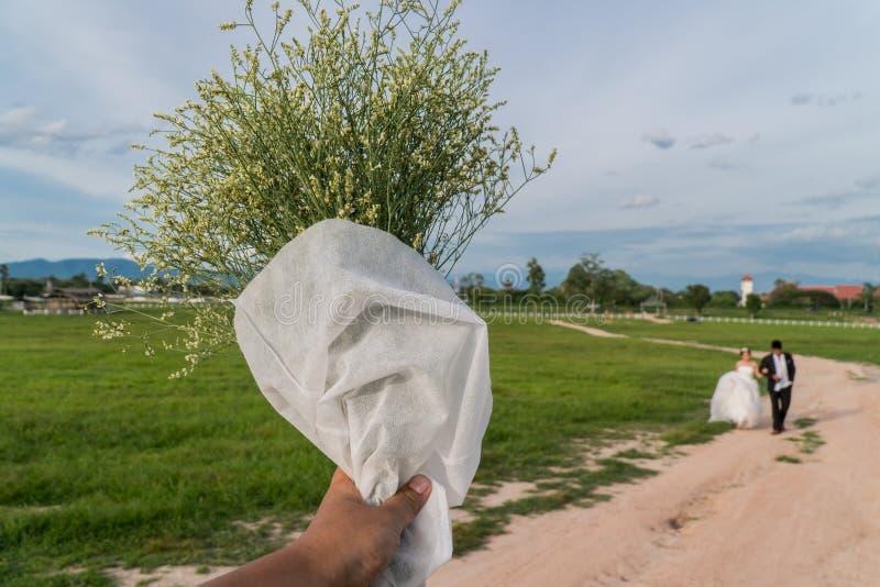 Os homens asiáticos entregam guardar as flores brancas aos pares do casamento foto de stock