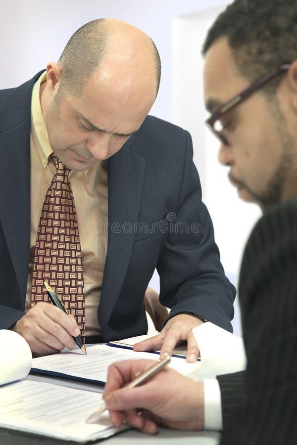 Os homens assinam o contrato imagem de stock