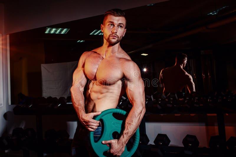 Os homens atléticos fortes musculares que bombeiam acima muscles e que treinam no gym Indivíduo considerável do halterofilista qu fotografia de stock royalty free