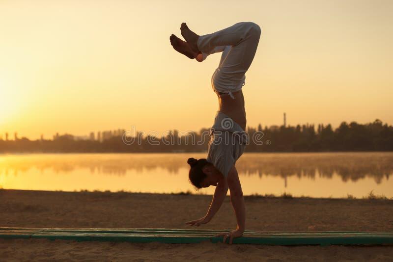 Os homens atléticos novos que estão na ioga levantam no lago próximo na paridade fotos de stock royalty free