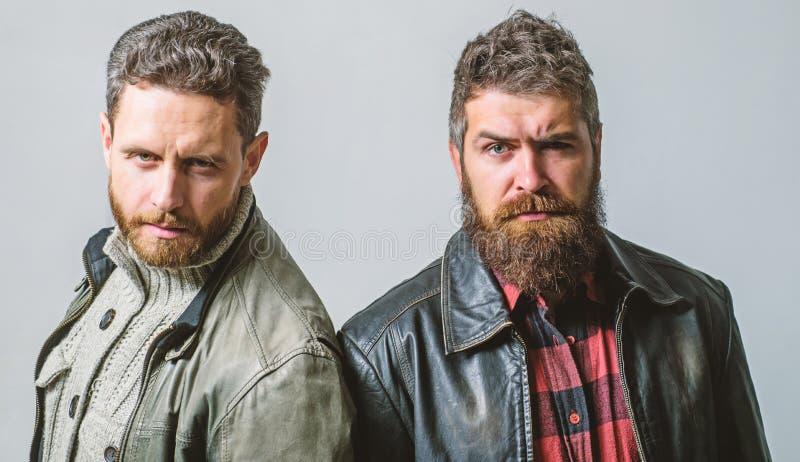Os homens brutais vestem casacos de cabedal r ? moda e fresco consider?veis E fotografia de stock