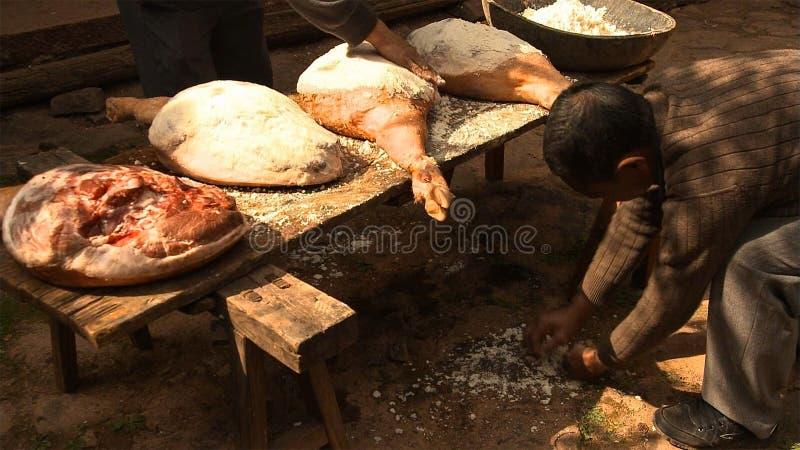 Os homens chineses espalham o sal uniformemente no presunto e pressionam-no repetidamente a fazer o presunto de Nuodeng yunnan Ch imagem de stock