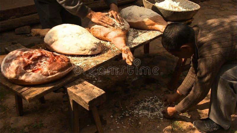 Os homens chineses espalham o sal uniformemente no presunto e pressionam-no repetidamente a fazer o presunto de Nuodeng yunnan Ch fotos de stock