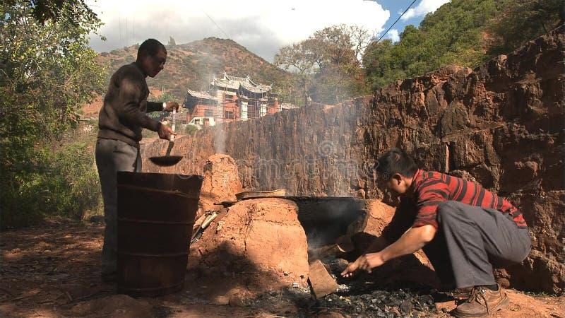 Os homens chineses fervem o sal, dobrando o sal cristalizado da água salgada fervida, trabalhando no campo de sal yunnan China fotos de stock royalty free