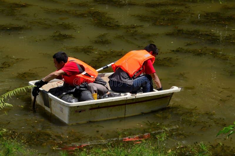 Os homens chineses no barco limpam o lago fotografia de stock