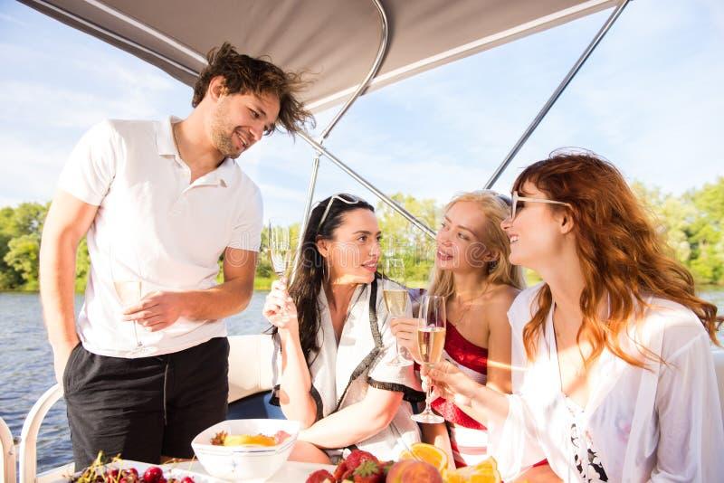 Os homens com as três meninas bonitas estão bebendo o champanhe no iate imagem de stock royalty free