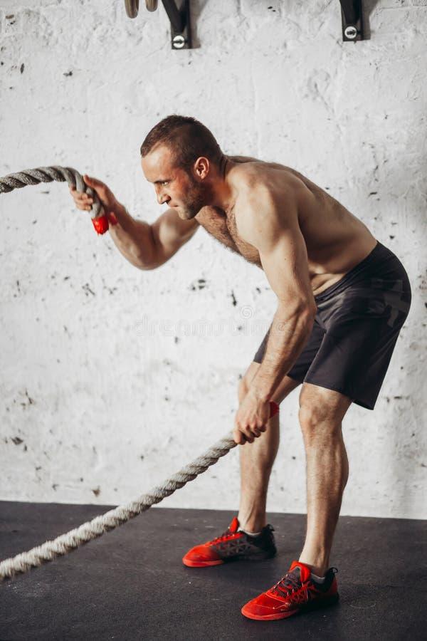 Os homens com corda da batalha lutam cordas exercitam no gym da aptidão foto de stock royalty free