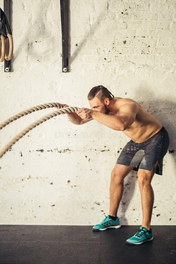 Os homens com corda da batalha lutam cordas exercitam no gym da aptidão fotos de stock royalty free
