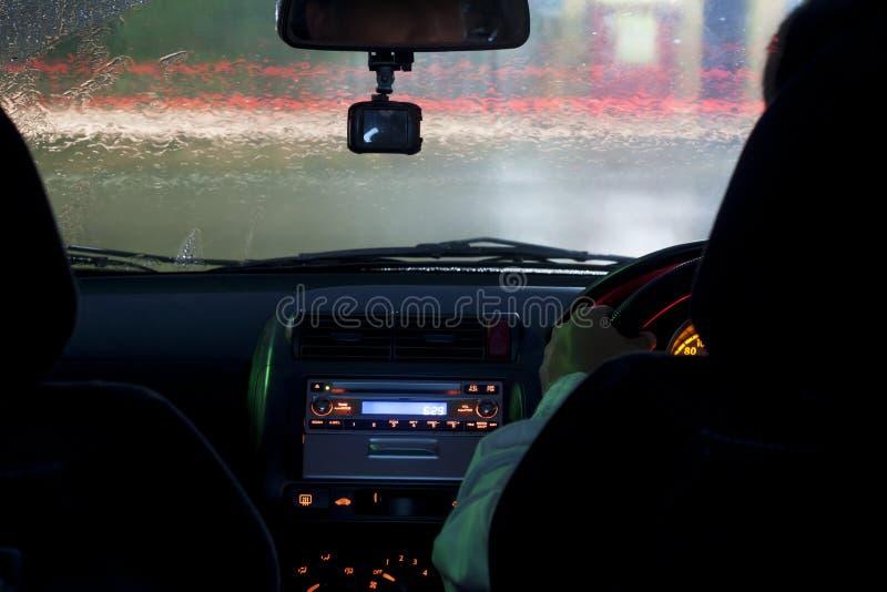 Os homens conduzem o carro no tempo chuvoso na noite fotografia de stock royalty free