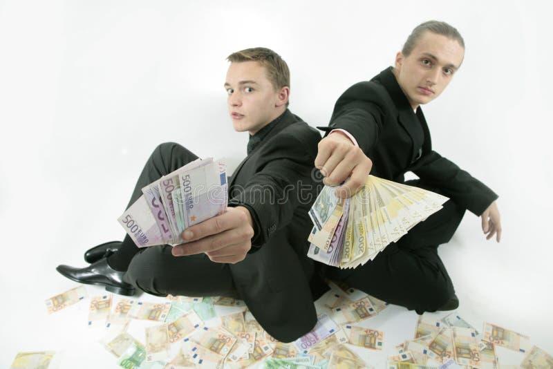 Os homens de negócios bem sucedidos oferecem o dinheiro imagens de stock royalty free
