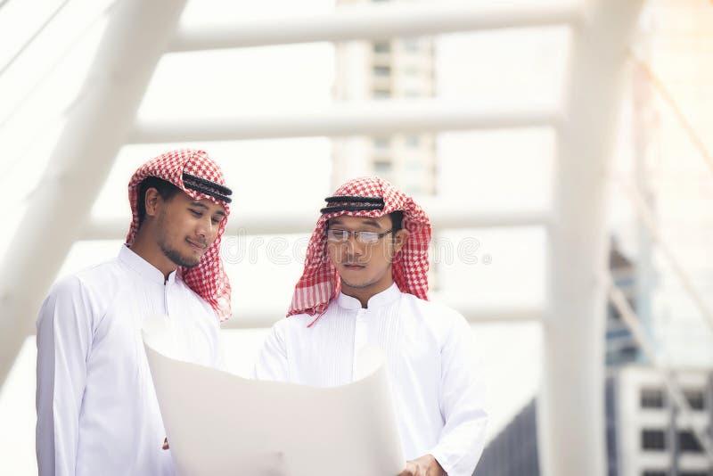 Os homens de negócios e os arquitetos árabes estão discutindo planos para c principal imagens de stock