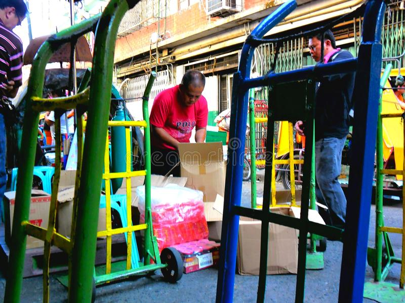 Os homens de negócios ou os comerciantes asiáticos tomam de sua mercadoria no quiapo, manila, Filipinas em Ásia foto de stock