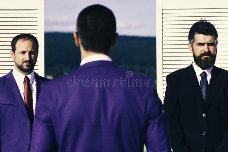Os homens de negócios vestem ternos e laços espertos na parede de madeira imagens de stock royalty free