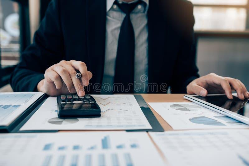 Os homens de neg?cios est?o usando calculadoras para calcular o lucro da empresa deduzindo das despesas e usando tabuletas para e imagens de stock royalty free