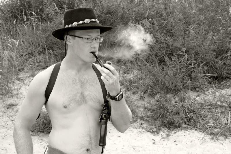 Os homens descamisado fumam uma tubulação imagem de stock