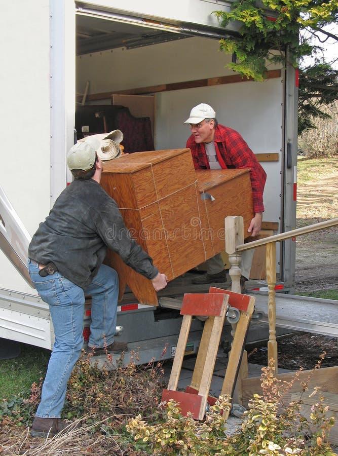 Os homens descarregam uma camionete movente imagens de stock