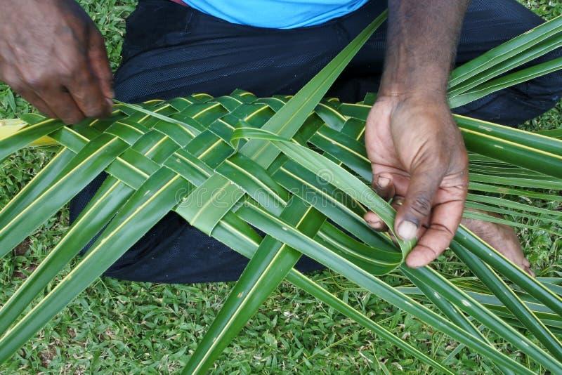 Os homens do Fijian criam uma cesta das folhas de palmeira de tecelagem de um coco foto de stock royalty free