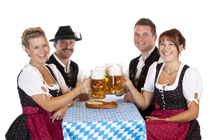 Os homens e as mulheres brindam com o stein da cerveja de Oktoberfest foto de stock royalty free