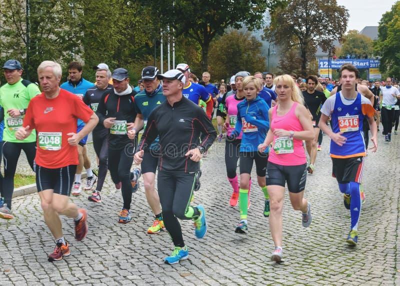 Os homens e as mulheres correm uma maratona Maratona em Alemanha, Magdeburgo, 18 oktober 2015 imagem de stock