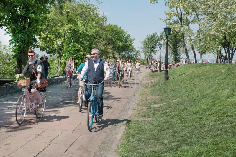 Os homens e as mulheres felizes ensolarados na forma velha denominam o ciclismo com a bicicleta do vintage no cruzeiro retro do f imagens de stock royalty free