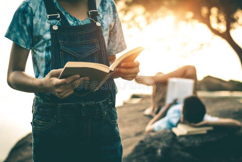 Os homens e as mulheres leram livros na natureza quieta fotografia de stock